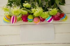 Uova di Pasqua dipinte, mazzo di fiore e busta su fondo di legno Immagine Stock Libera da Diritti