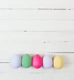 Uova di Pasqua dipinte nei colori pastelli su legno bianco Immagine Stock