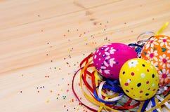 Uova di Pasqua dipinte in un nido di erba e dei nastri Immagini Stock Libere da Diritti