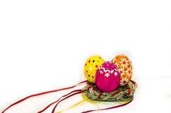 Uova di Pasqua dipinte in un nido di erba e dei nastri Fotografie Stock