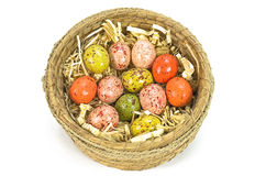 Uova di Pasqua dipinte variopinte in canestro marrone isolato su fondo bianco Fotografia Stock Libera da Diritti