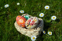 Uova di Pasqua dipinte variopinte su un canestro su un'erba verde Fotografie Stock
