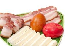 Uova di Pasqua e bacon e feta sistemati su un piatto verde fotografia stock