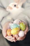 Uova di Pasqua e coniglio variopinte in mani del bambino Fotografie Stock Libere da Diritti