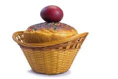 Uova di Pasqua e pane rossi di Pasqua in un canestro su un backgrou bianco Immagini Stock