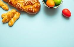 Uova di Pasqua e treccia di tsoureki, pane dolce greco di pasqua, su fondo blu immagini stock libere da diritti