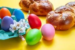 Uova di Pasqua e treccia di tsoureki, pane dolce greco di pasqua, su fondo giallo fotografia stock