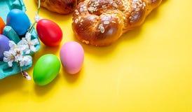 Uova di Pasqua e treccia di tsoureki, pane dolce greco di pasqua, su fondo giallo fotografie stock