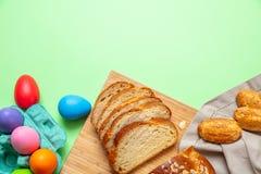 Uova di Pasqua e treccia di tsoureki, pane dolce greco di pasqua, su pastello verde immagine stock