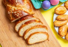 Uova di Pasqua e treccia di tsoureki, pane dolce greco di pasqua, sul fondo giallo di colore fotografia stock libera da diritti