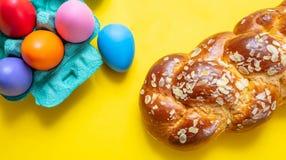 Uova di Pasqua e treccia di tsoureki, pane dolce greco di pasqua, sul fondo giallo di colore fotografie stock libere da diritti