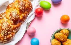 Uova di Pasqua e treccia di tsoureki, pane dolce greco di pasqua, sul fondo rosa di colore fotografie stock libere da diritti