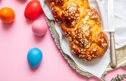 Uova di Pasqua e treccia di tsoureki, pane dolce greco di pasqua, sul fondo rosa di colore fotografie stock