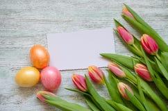 Uova di Pasqua e tulipani con una carta bianca sui precedenti di legno d'annata Immagini Stock Libere da Diritti