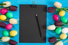 Uova di Pasqua e tulipani variopinte su fondo di legno rustico blu Immagine Stock