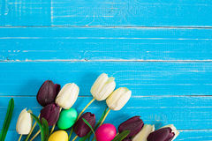 Uova di Pasqua e tulipani variopinte su fondo di legno rustico blu Fotografia Stock Libera da Diritti