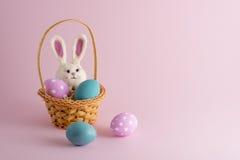 4 uova di Pasqua e un coniglietto in piccolo canestro su fondo rosa Fotografia Stock