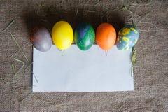 Uova di Pasqua e un pezzo di Libro Bianco Immagine Stock