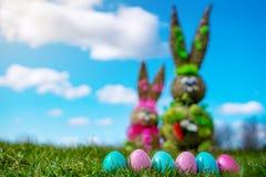 Uova di Pasqua erba verde di Straw Figure Bunny With Colorful e cielo blu Pasqua e fondo della primavera fotografia stock libera da diritti