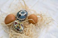 Uova di Pasqua fatte a mano tradizionali in paglia sul panno bianco Fotografie Stock Libere da Diritti