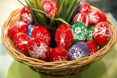 Uova di Pasqua fatte a mano variopinte in un canestro di legno come pasqua prese Fotografia Stock