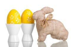 Uova di Pasqua gialle in tazze e coniglietto isolato su bianco Fotografia Stock Libera da Diritti