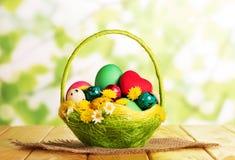 Uova di Pasqua merce nel carrello, cuore, fiori, panno, su verde astratto Fotografia Stock