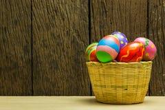 Uova di Pasqua merce nel carrello e fondo di legno Fotografia Stock