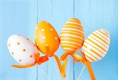 Uova di Pasqua modellate arancia su fondo blu Fotografia Stock Libera da Diritti