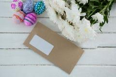 Uova di Pasqua multicolori, mazzo di fiore e busta su fondo di legno Immagini Stock Libere da Diritti