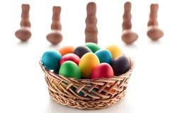 Uova di Pasqua multicolori in un canestro, su una tavola di legno bianca, w Immagini Stock Libere da Diritti
