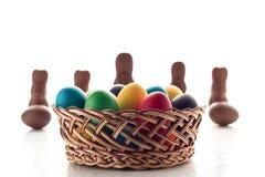 Uova di Pasqua multicolori in un canestro, su una tavola di legno bianca, w Fotografia Stock Libera da Diritti