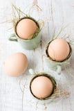 Uova di Pasqua naturali non colorate in tazze del caffè espresso; concetto felice di pasqua; fondo di legno bianco Immagine Stock Libera da Diritti
