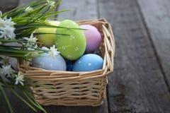 Uova di Pasqua nel canestro dei bordi di legno Fotografie Stock Libere da Diritti