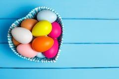 Uova di Pasqua nel canestro dei bordi di legno Immagini Stock