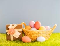 Uova di Pasqua nel canestro su erba verde fotografie stock