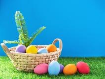 Uova di Pasqua nel canestro su erba verde fotografia stock