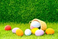 Uova di Pasqua nel canestro su erba verde immagini stock