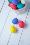 Uova di Pasqua nel canestro sui bordi di legno su un fondo bianco Fine in su Fotografie Stock