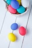 Uova di Pasqua nel canestro sui bordi di legno su un fondo bianco Fine in su Colpo verticale Immagine Stock Libera da Diritti