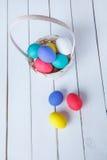 Uova di Pasqua nel canestro sui bordi di legno su un fondo bianco Vista da sopra Fotografia Stock Libera da Diritti