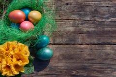 Uova di Pasqua in nido su vecchio fondo di legno Immagine Stock