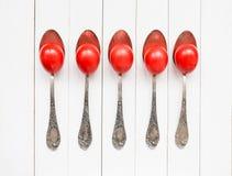 Uova di Pasqua rosse in vecchi cucchiai Fotografia Stock