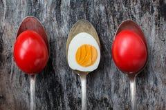 Uova di Pasqua rosse in vecchi cucchiai su fondo di legno Immagini Stock Libere da Diritti