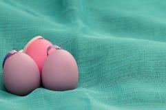 Uova di Pasqua su ciano fondo Uova di Pasqua decorative porpora su struttura blu del fondo Uovo porpora con la ciotola su ciano Immagini Stock Libere da Diritti