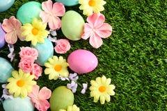 Uova di Pasqua su erba con il fondo dei fiori Fotografia Stock Libera da Diritti
