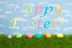 Uova di Pasqua su erba, fondo del cielo, testo felice di Pasqua Immagini Stock Libere da Diritti