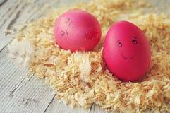 Uova di Pasqua su segatura di legno due uova di Pasqua divertentesi con le persone tirate Immagini Stock Libere da Diritti