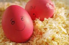 Uova di Pasqua su segatura di legno due uova di Pasqua divertentesi con le persone tirate Allegro e l'uovo tagliato triste Immagini Stock Libere da Diritti