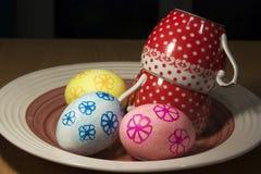 Uova di Pasqua su un piatto con due tazze ceramiche Immagini Stock Libere da Diritti